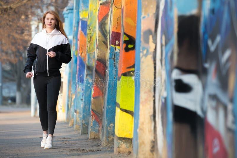 Ragazza che cammina durante la pratica di sport di mattina immagini stock libere da diritti