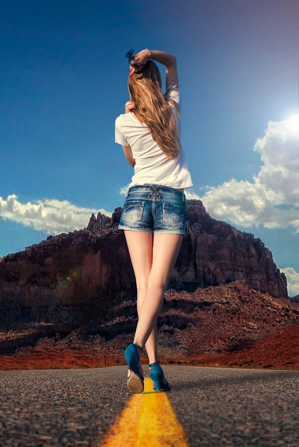 Ragazza che cammina lungo la strada nel deserto fotografie stock