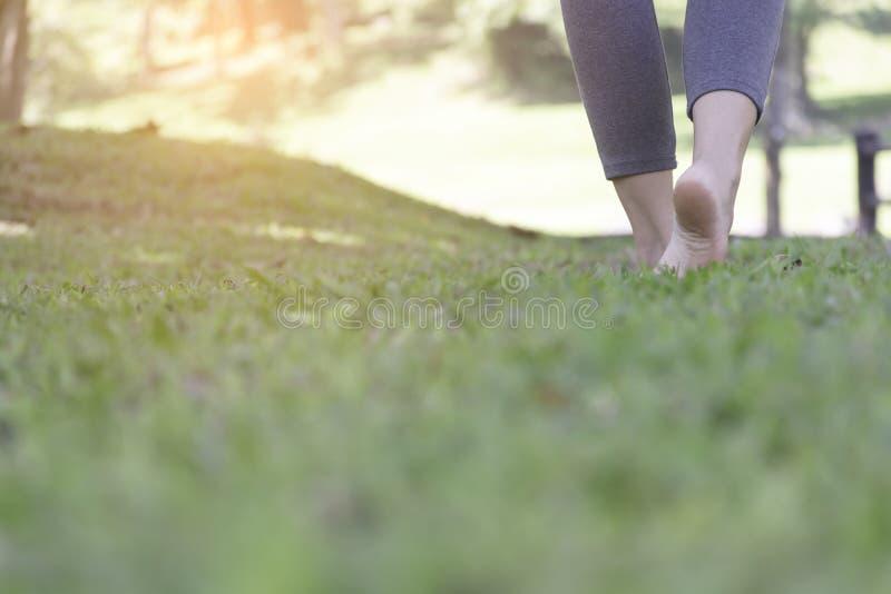 Ragazza che cammina a piedi nudi sull'erba verde fotografia stock libera da diritti