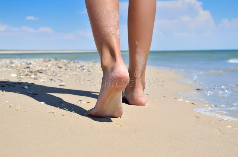 Ragazza che cammina a piedi nudi sulla sabbia della spiaggia del mare immagine stock