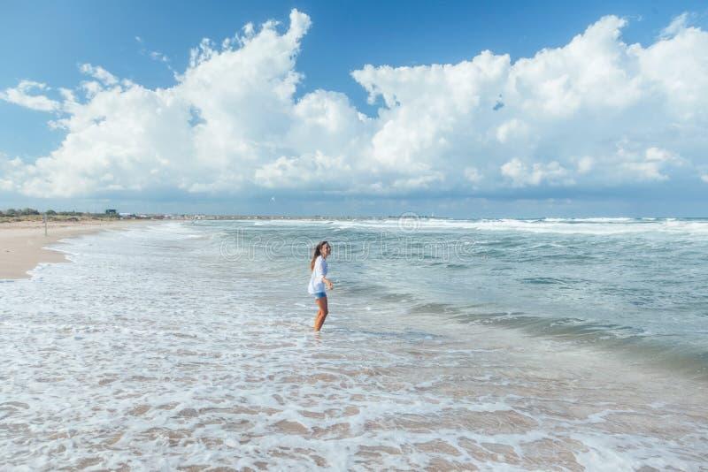 Ragazza che cammina sulla spiaggia fotografie stock