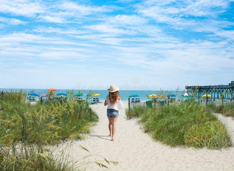 Ragazza che cammina sulla spiaggia sulle vacanze estive immagini stock libere da diritti