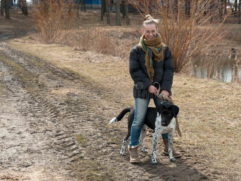 Ragazza che cammina un grande cane cieco in primavera fotografie stock