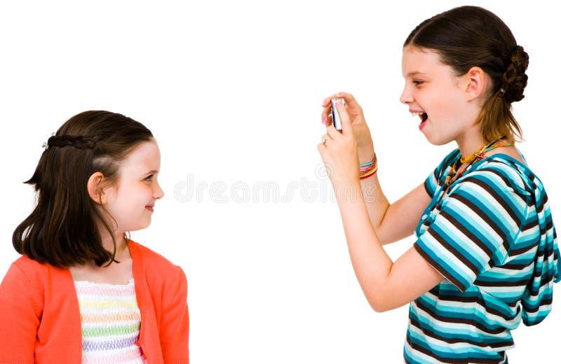 Ragazza che cattura maschera della sorella fotografie stock