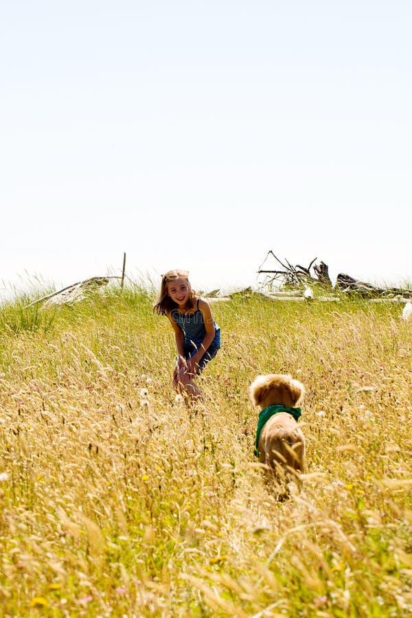 Ragazza che chiama il suo cucciolo in un campo di erba immagini stock