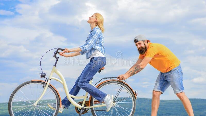 Ragazza che cicla mentre il ragazzo la sostiene Insegni all'adulto a guidare la bici Gli aiuti dell'uomo tengono l'equilibrio e g fotografie stock libere da diritti