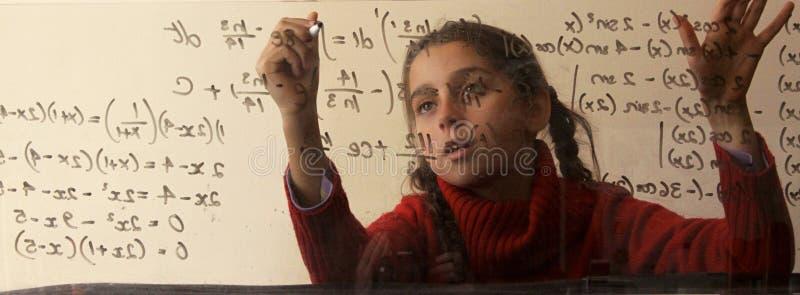 Ragazza che completa le equazioni matematiche sul bordo di vetro fotografia stock