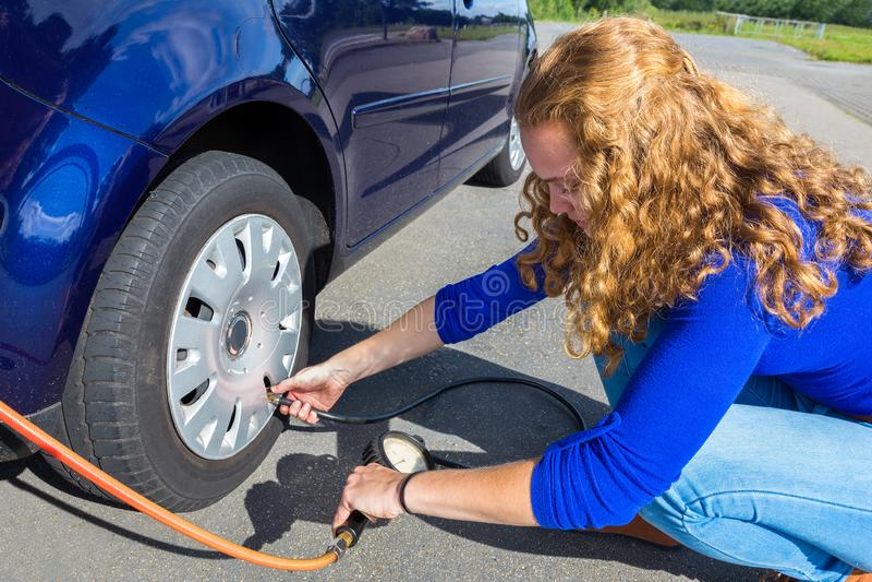 Ragazza che controlla pressione d'aria della gomma di automobile immagine stock