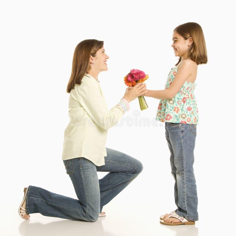 Ragazza che dà i fiori della madre. fotografie stock