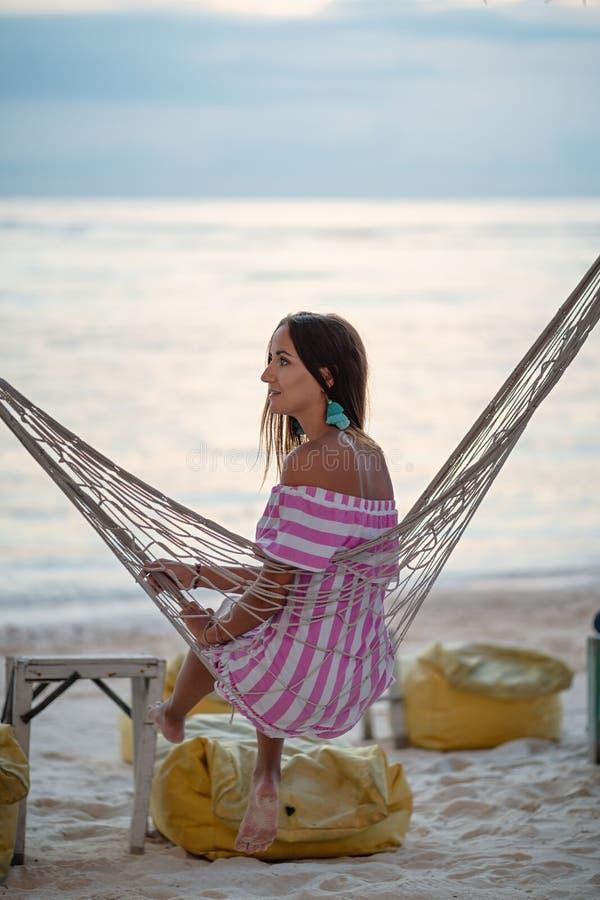 Ragazza che distoglie lo sguardo sedentesi in un'amaca sulla spiaggia nella sera immagini stock