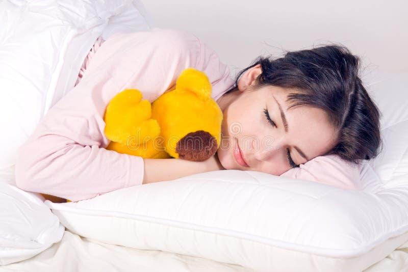 Ragazza che dorme con l'orso di orsacchiotto fotografie stock