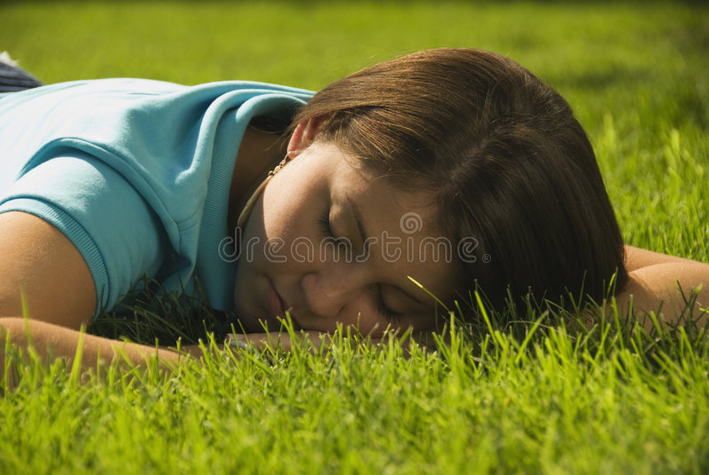 Ragazza che dorme nell'erba fotografia stock libera da diritti