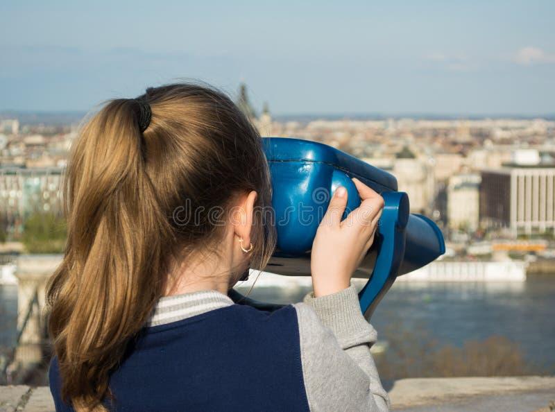 Ragazza che esamina binoculare a gettoni a Budapest fotografie stock