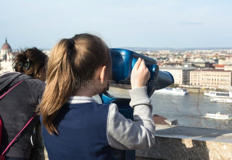 Ragazza che esamina binoculare a gettoni a Budapest immagini stock libere da diritti