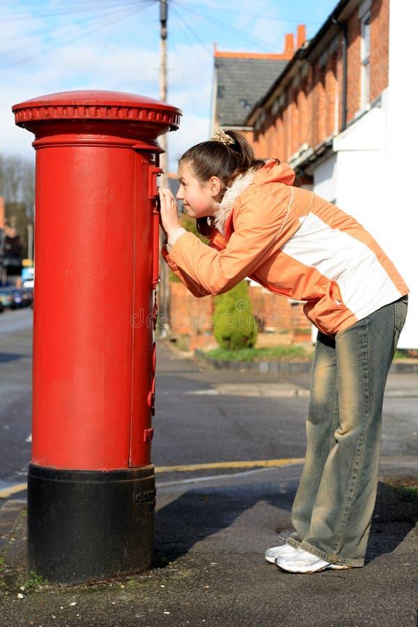 Ragazza che esamina foro del postbox britannico rosso fotografie stock