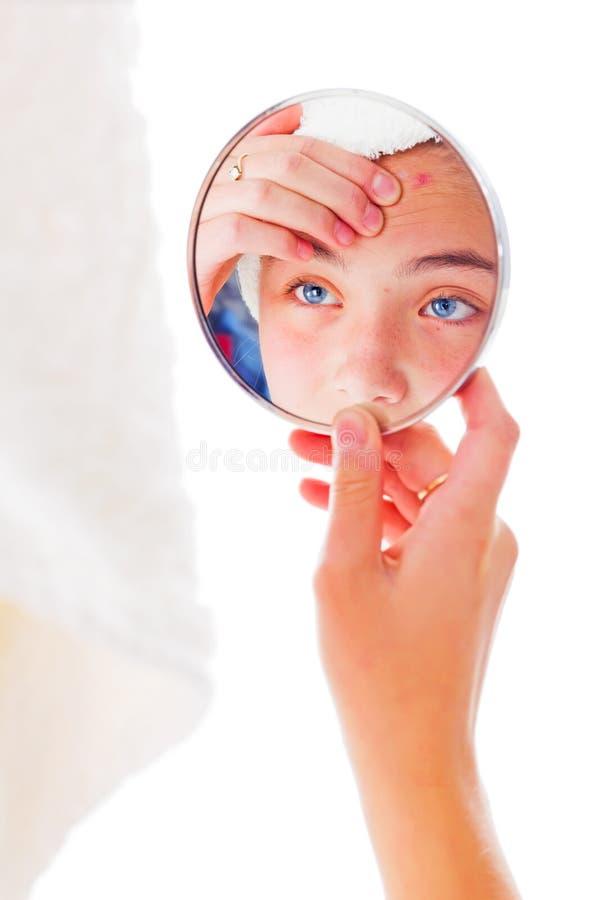 Ragazza che esamina i suoi brufoli nello specchio fotografia stock