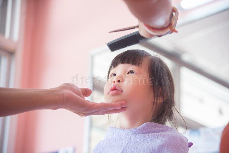 Ragazza che esamina le forbici mentre taglio del parrucchiere immagini stock