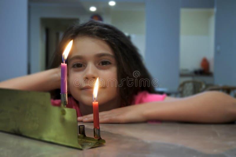 Ragazza che esamina le prime candele della festa ebrea di hanukkah sopra fotografia stock libera da diritti