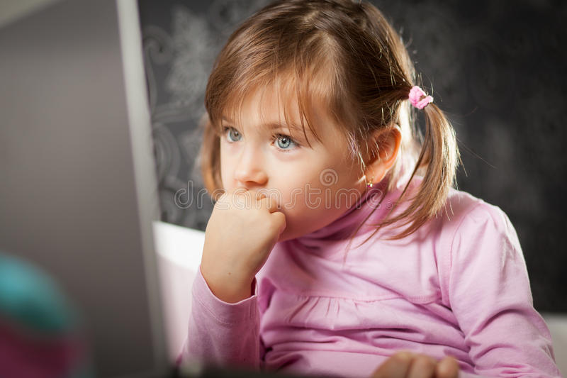 Ragazza che esamina lo schermo del computer portatile immagini stock