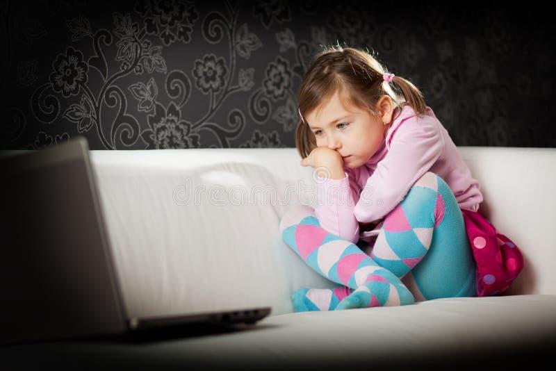 Ragazza che esamina lo schermo del computer portatile fotografia stock libera da diritti