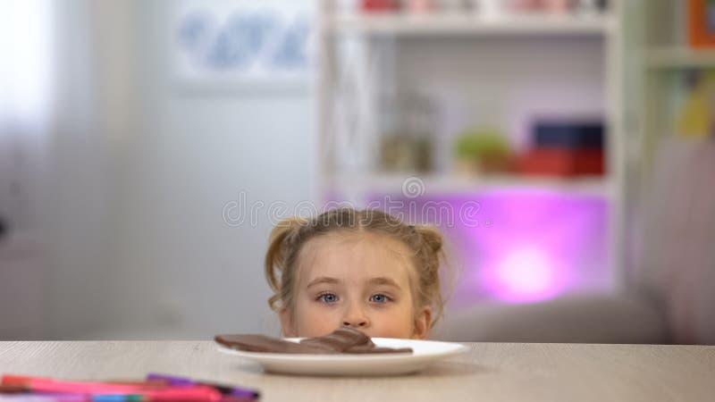 Ragazza che esamina segreto cioccolato da sotto la tavola, tentativo di rubare i dolci immagine stock