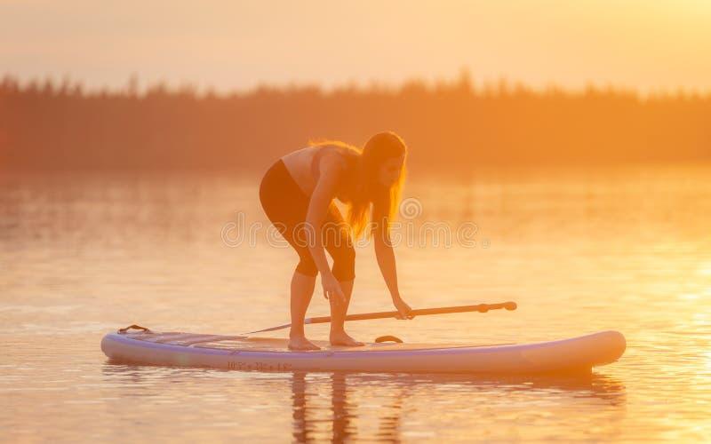 Ragazza che esercita yoga sul paddleboard nel tramonto sul lago scenico Velke Darko immagine stock libera da diritti