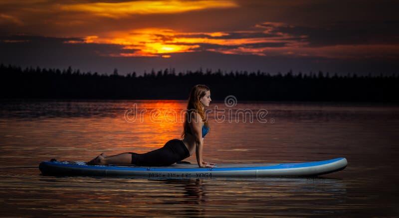 Ragazza che esercita yoga sul paddleboard nel tramonto sul lago scenico Velke Darko fotografie stock