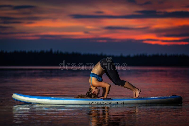 Ragazza che esercita yoga sul paddleboard nel tramonto sul lago scenico Velke Darko fotografia stock