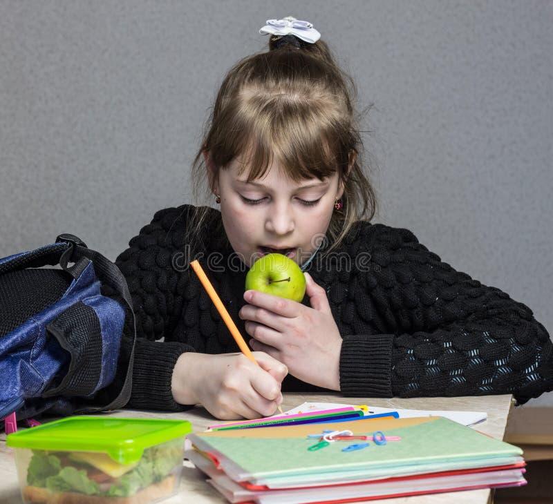 Ragazza che fa compito e che mangia mela, mela verde e scolara facenti compito immagini stock libere da diritti