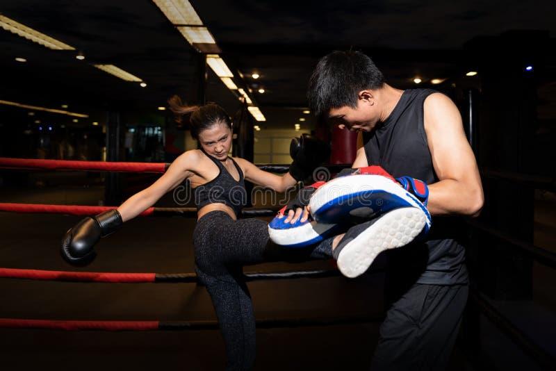 Ragazza che fa esercizio di scossa durante l'addestramento di kickboxing con l'istruttore personale fotografia stock libera da diritti