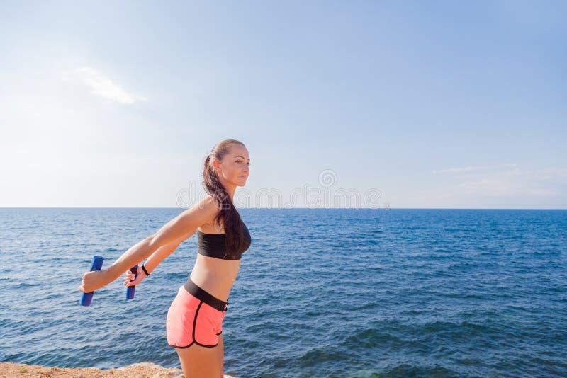 Ragazza che fa gli esercizi di forma fisica con le teste di legno fotografie stock libere da diritti