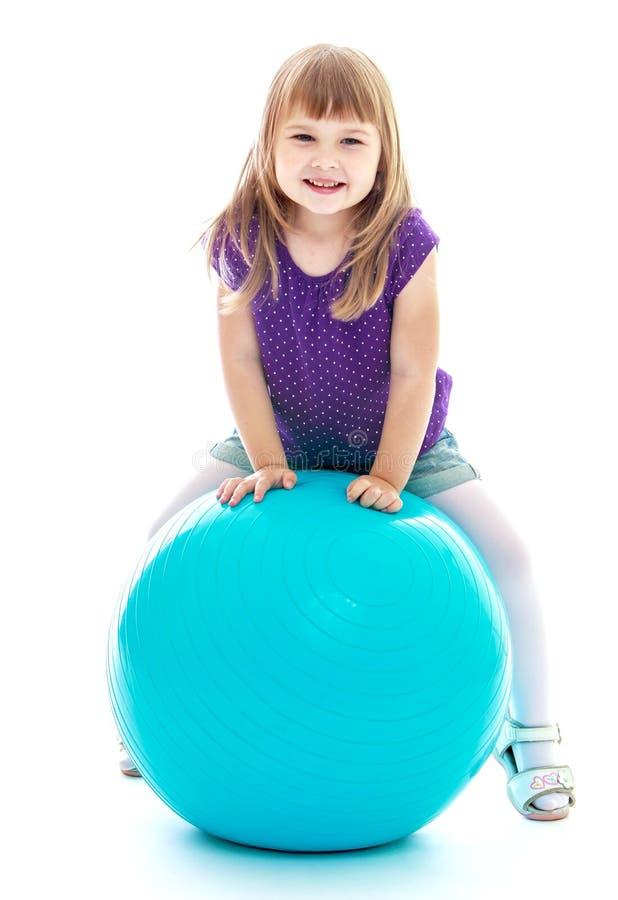 Ragazza che fa gli esercizi sulla grande palla blu fotografia stock