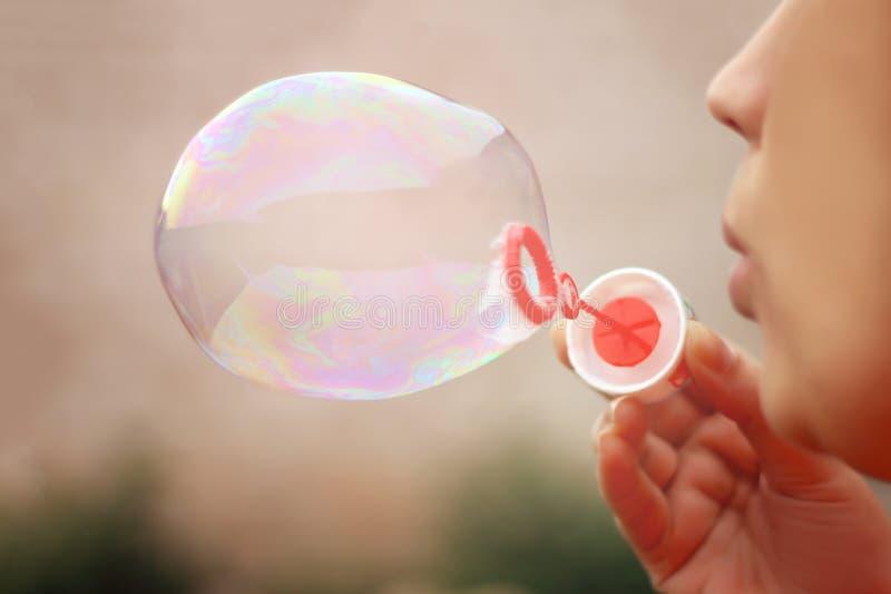 Ragazza che fa le bolle di sapone, primo piano immagine stock