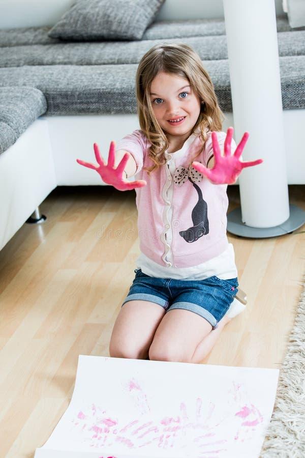 Ragazza che fa le stampe rosa della mano sulla carta fotografie stock