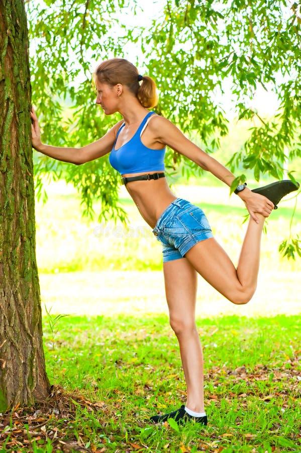 Ragazza che fa riscaldamento al parco dell'albero in abiti sportivi fotografia stock libera da diritti