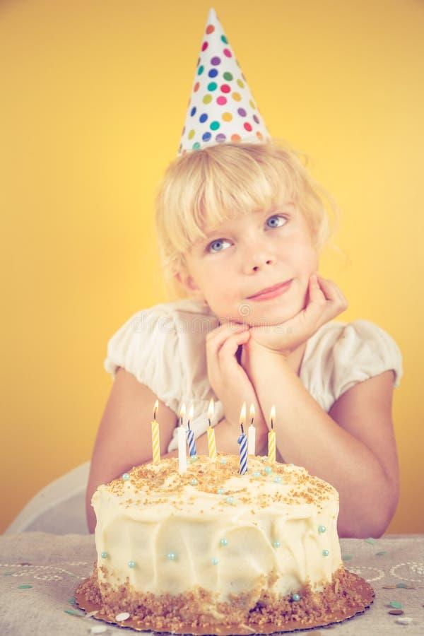 Ragazza che fa un desiderio dalla torta di compleanno Celebrazione della festa di compleanno immagini stock