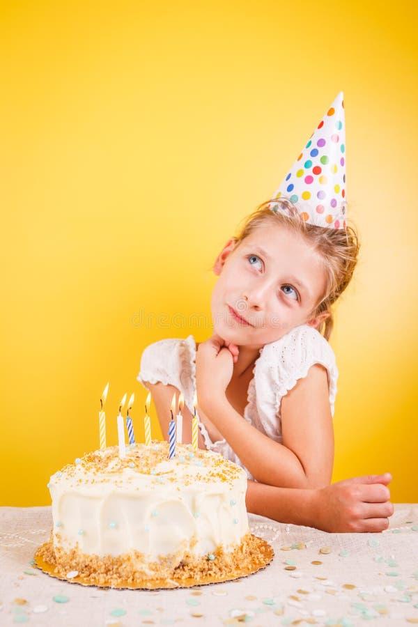Ragazza che fa un desiderio dalla torta di compleanno Celebrazione della festa di compleanno fotografia stock