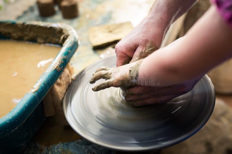 Ragazza che fa una ciotola dell'argilla sullo scolpire ruota fotografia stock libera da diritti