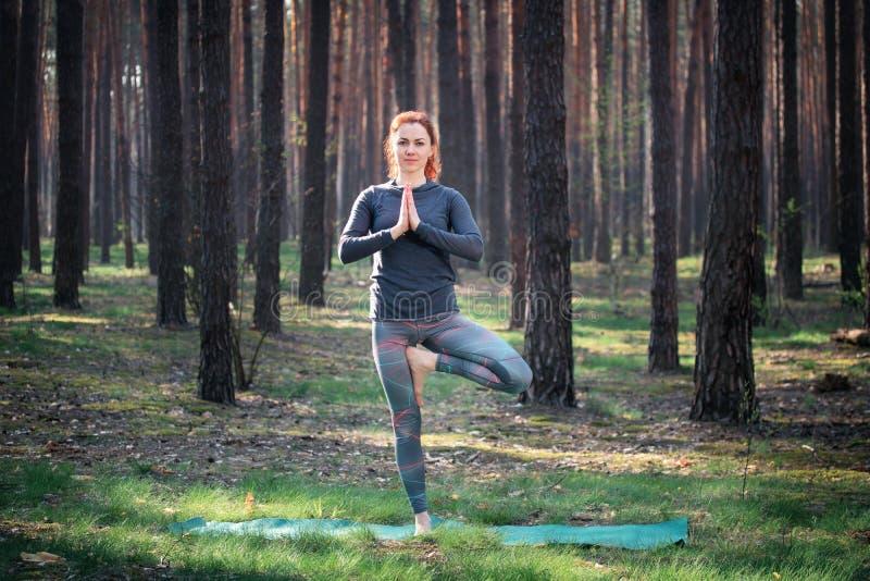 Ragazza che fa yoga nella foresta in natura immagine stock