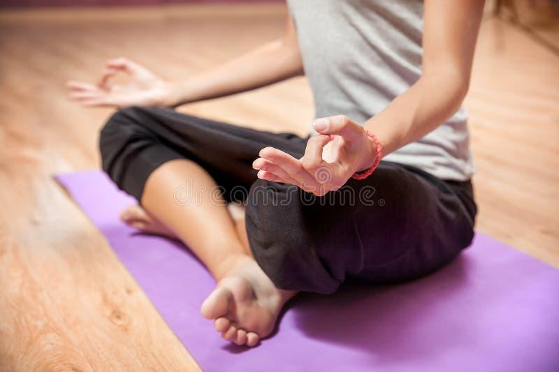 Ragazza che fa yoga in primo piano di posizione di loto all'interno fotografia stock libera da diritti