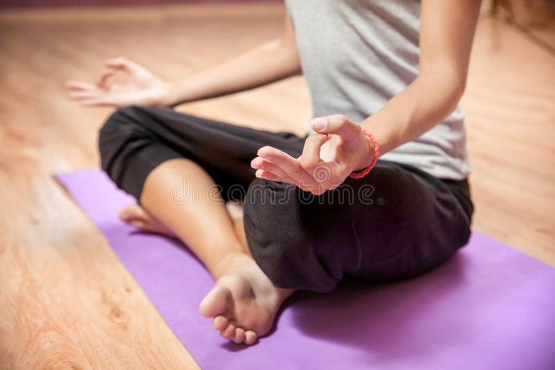 Ragazza che fa yoga in primo piano di posizione di loto all'interno immagine stock libera da diritti