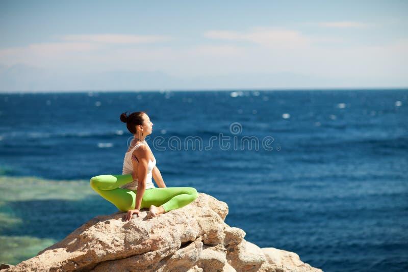 Ragazza che fa yoga sulla spiaggia immagini stock libere da diritti