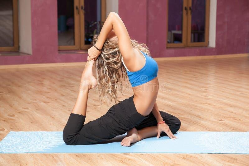 Ragazza che fa yoga sulla stuoia all'interno fotografie stock