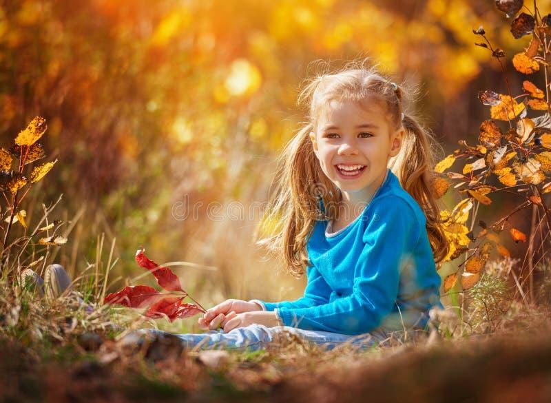 Ragazza che gioca in autunno fotografie stock libere da diritti