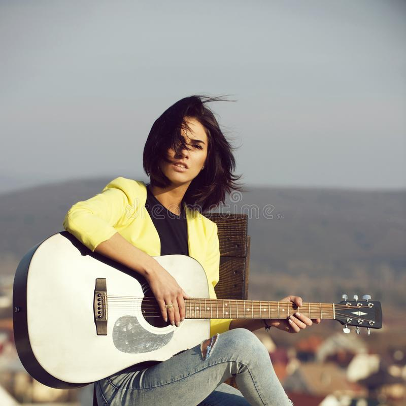 Ragazza che gioca chitarra su cielo blu fotografia stock