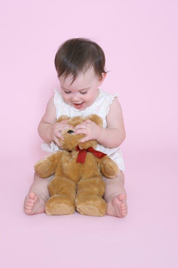Ragazza che gioca con gli occhi nascosti dell'orso di orsacchiotto fotografie stock libere da diritti