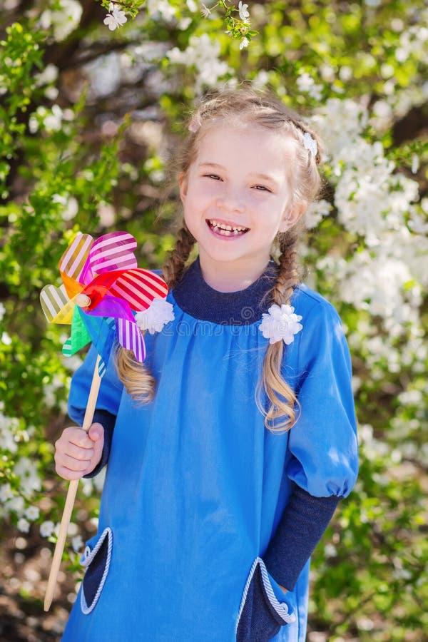 Ragazza che gioca con il mulino a vento nei precedenti di un albero di fioritura fotografia stock libera da diritti