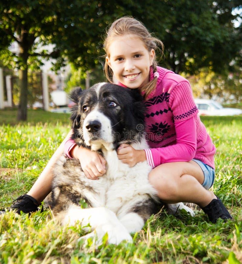 Ragazza che gioca con il suo cane fotografia stock