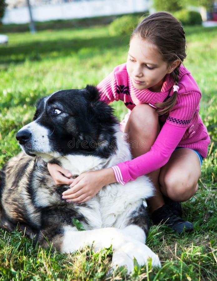 Ragazza che gioca con il suo cane fotografia stock libera da diritti