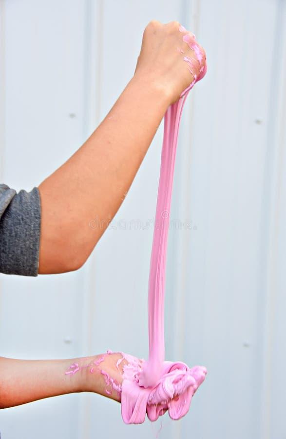 Ragazza che gioca con la melma rosa immagine stock